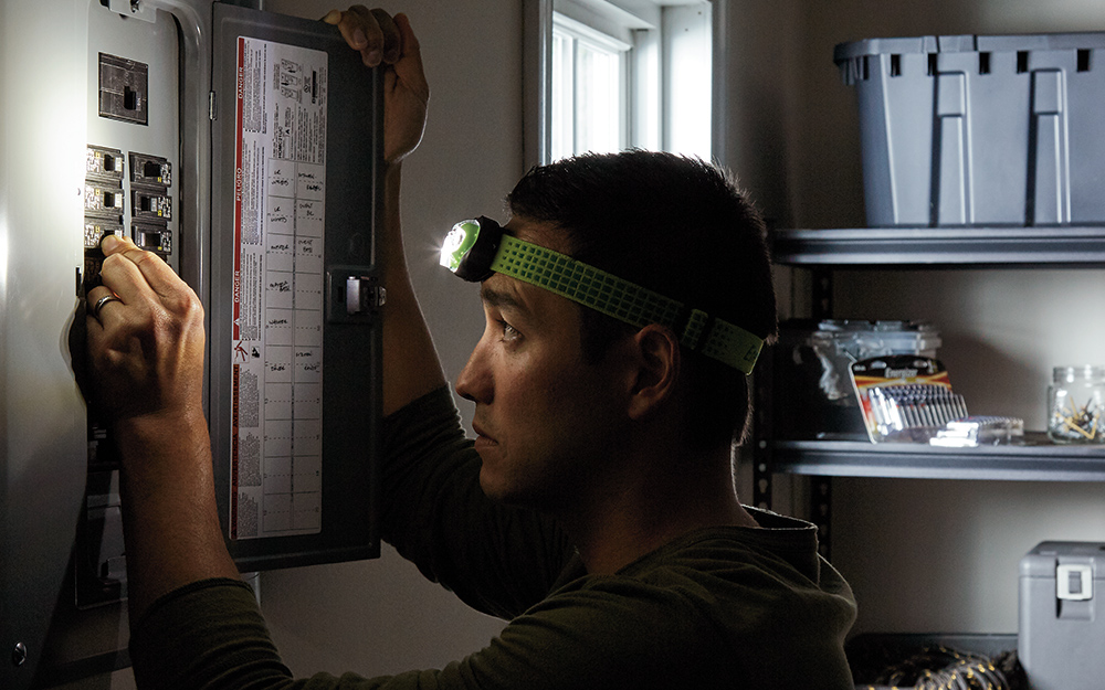 A person wearing a headlamp while adjusting a circuit breaker in an electrical panel.