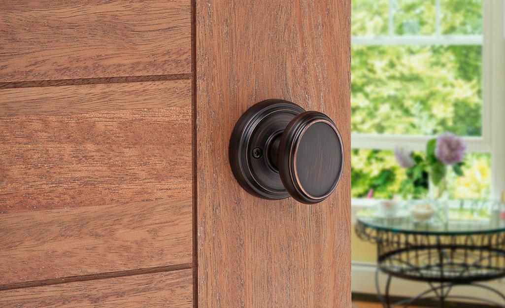 A dummy door knob on a wood door.