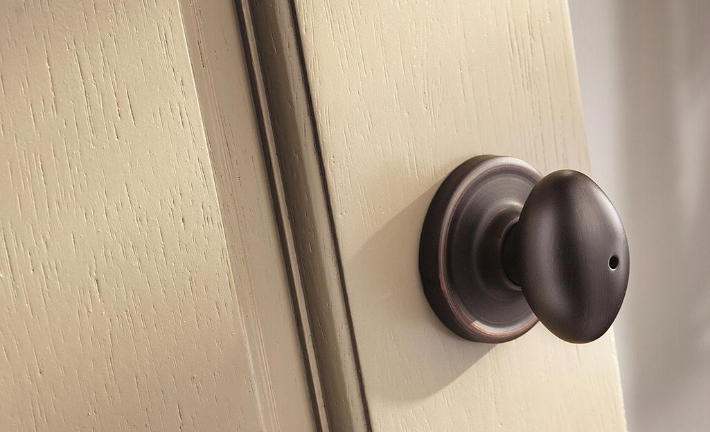 A privacy door knob on an off-white door.