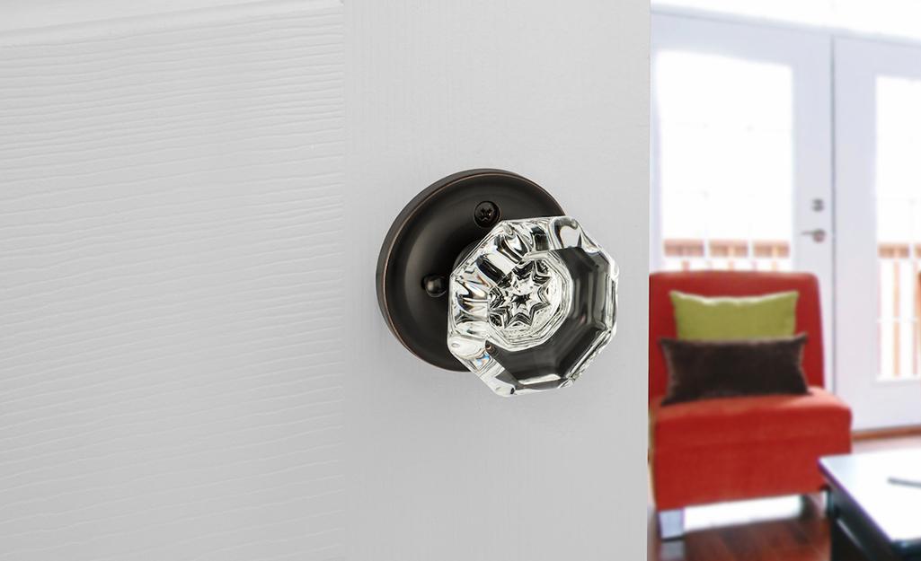 A crystal door knob on a white door.