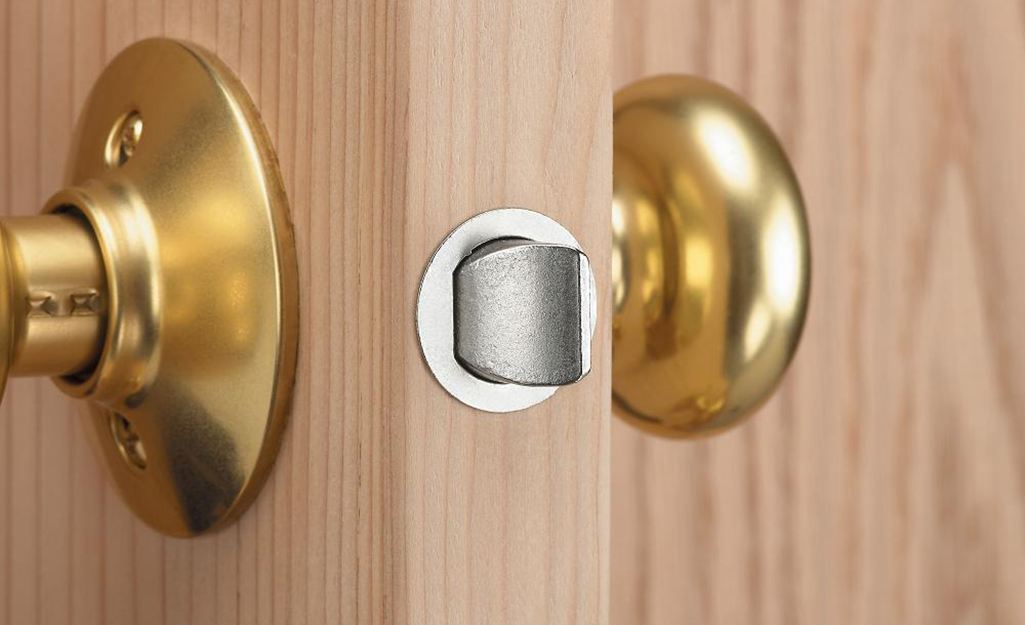 The edge of a door with brass-colored door knobs.