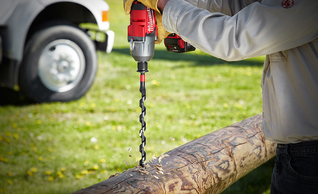 Someone using an auger drill bit on a log.