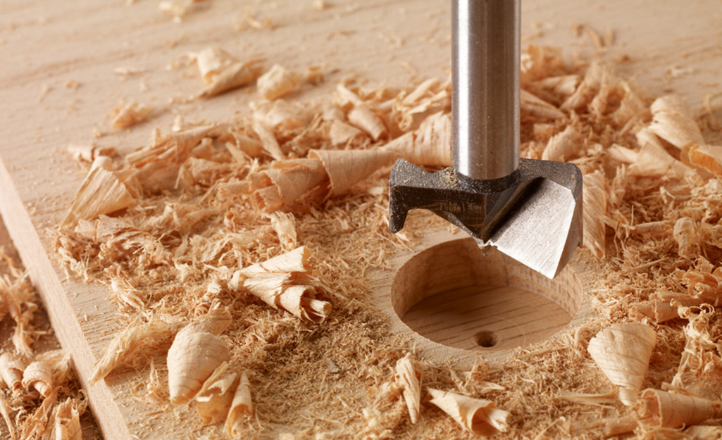 A Forstner drill bit being using to make a hole in a board.