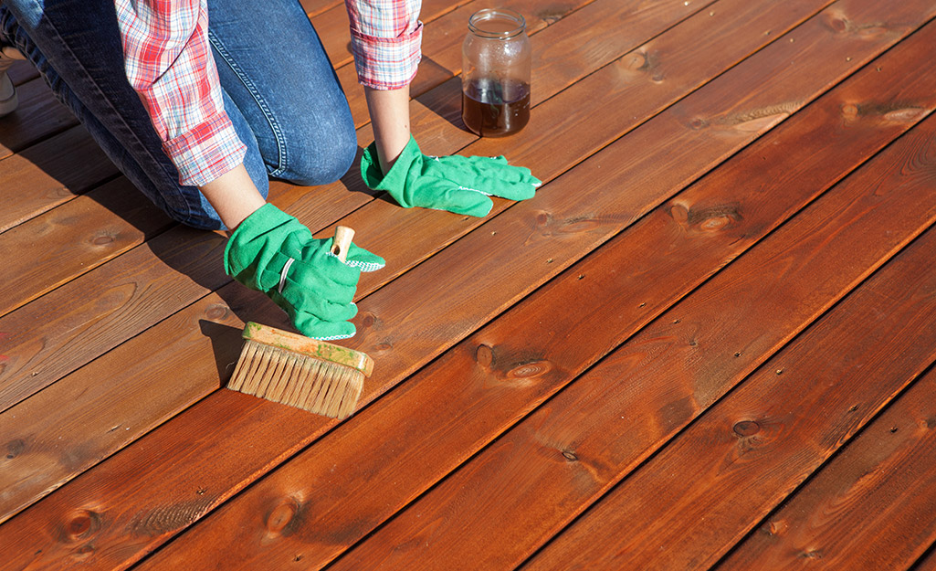 A person using an exterior wood sealer on a deck.