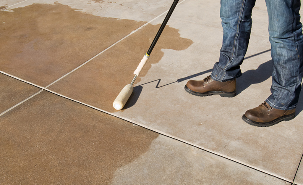A person using a roller brush to waterproof concrete.