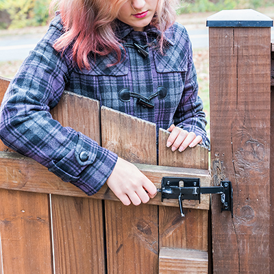 A person latching the gate of a wood fence.