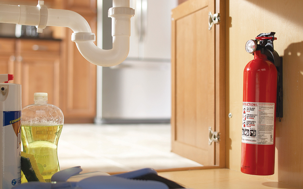 a fire extinguisher inside of a kitchen cabinet.