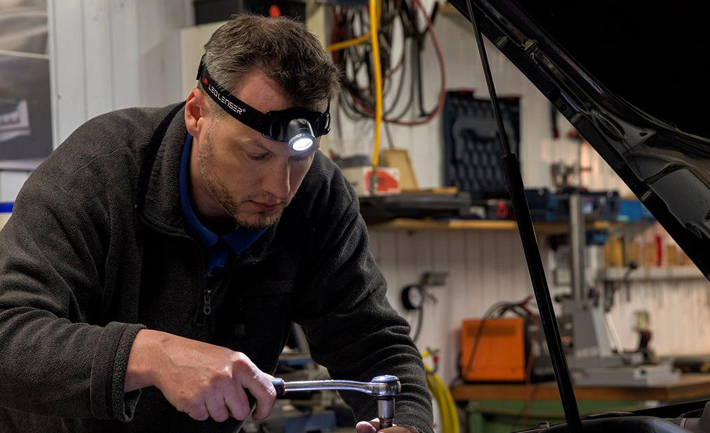 A man wears a headlamp flashlight to fix a car engine.