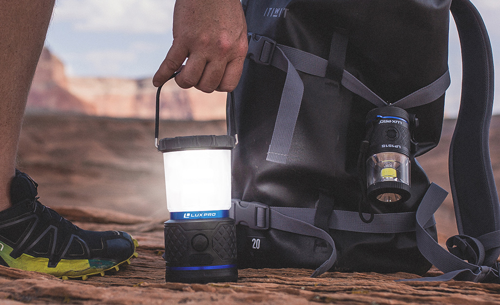 A lantern flashlight powered on is used by a hiker.