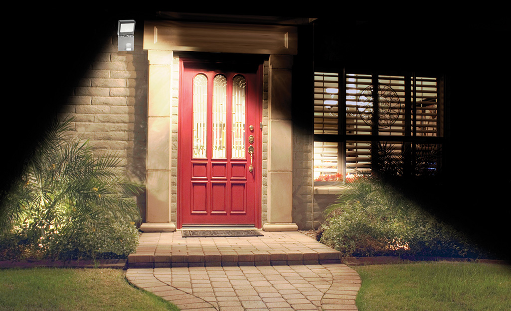 A spotlight shines on a front door and walkway.