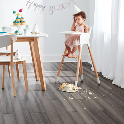 A little girl eats a birthday cake in a kitchen with vinyl flooring.