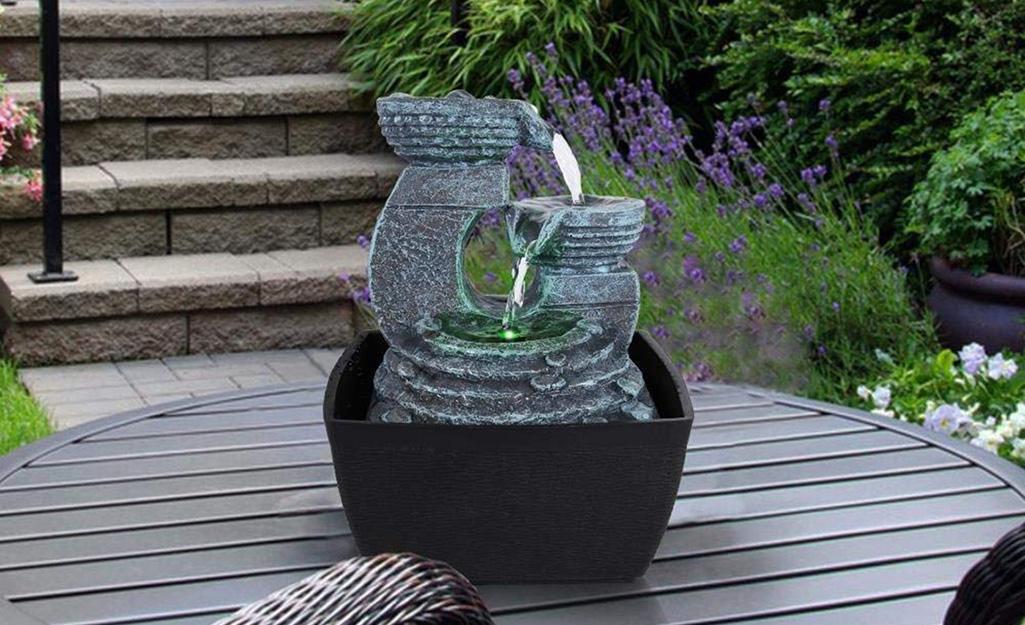 A tabletop fountain on an outdoor table on a patio.