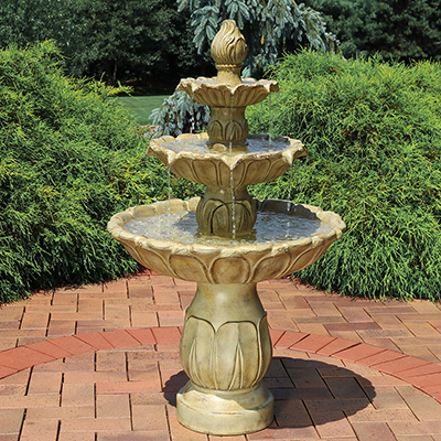 A tiered water fountain on a brick patio in a garden.