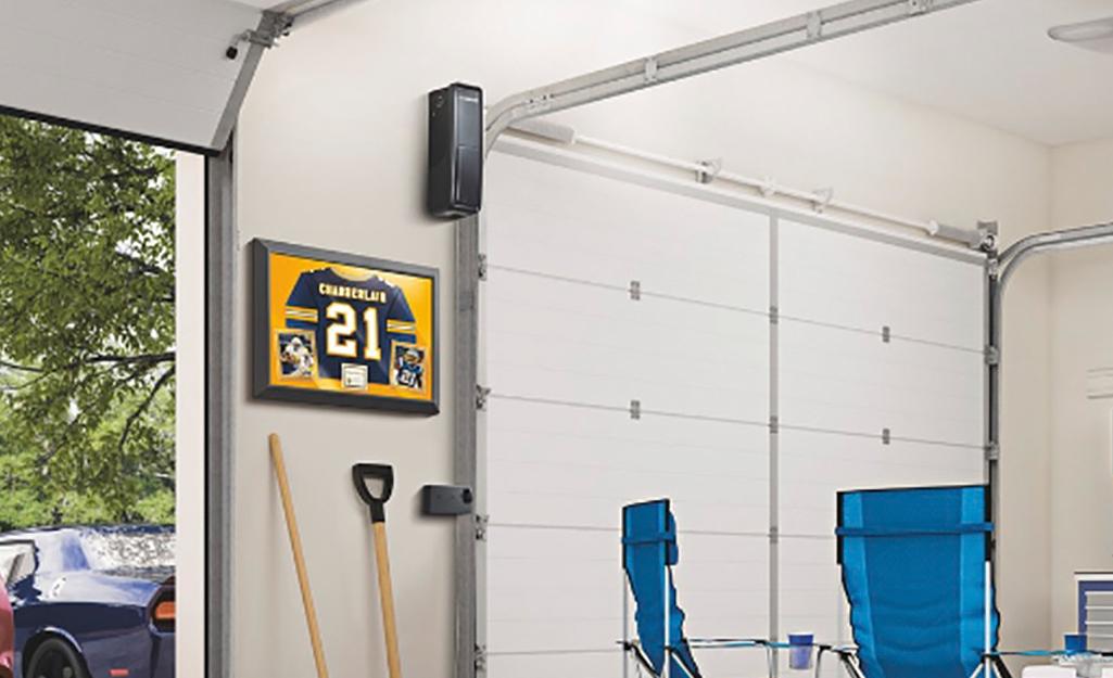 A wall mount garage door opener hangs on a garage wall.