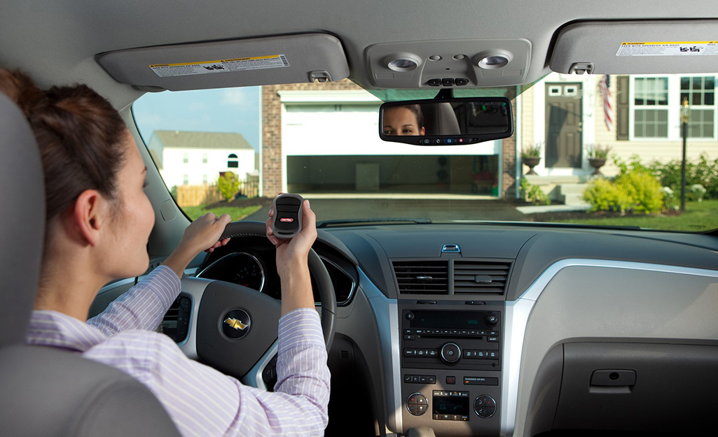 A person uses a mobile device to activate a smart garage door opener.