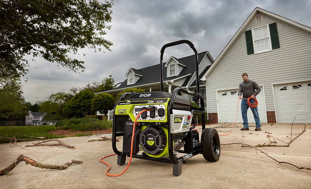 A man uses a portable generator in his driveway.
