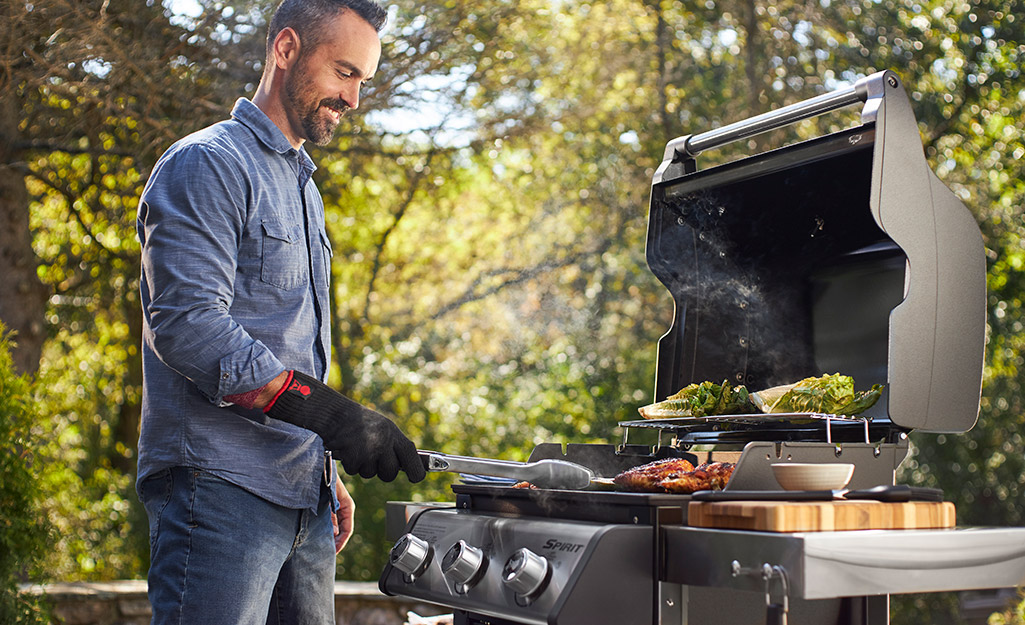 Man stands at grill filled with food
