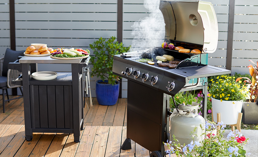 Meat and vegetables cooking on a gas grill.
