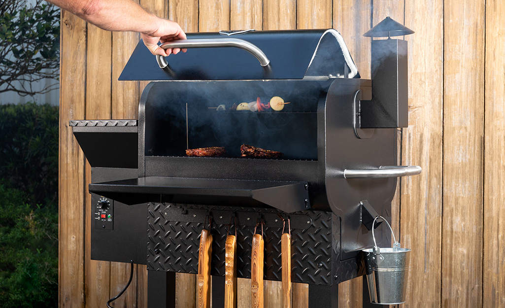 A person adjusting food in a smoker.
