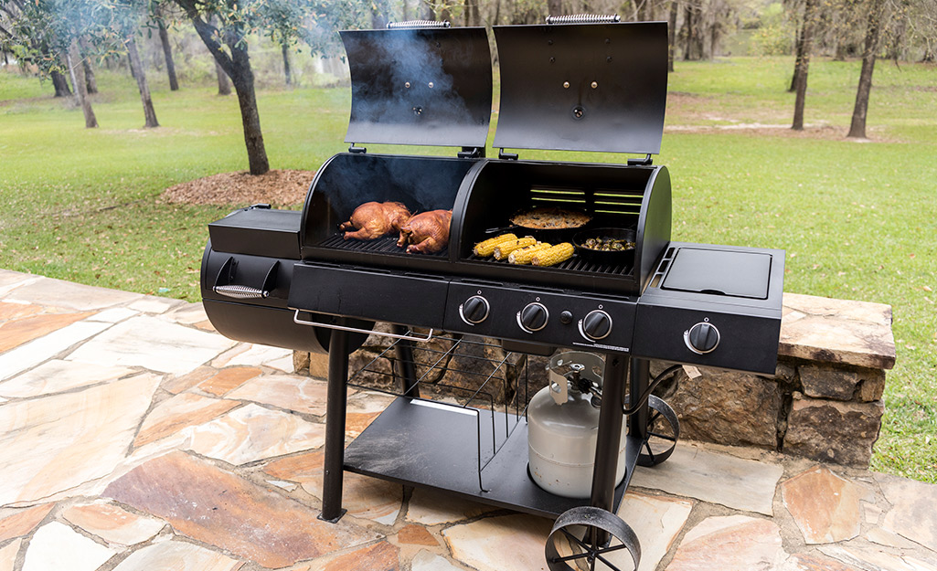 A variety of food cooking in grill-smoker.
