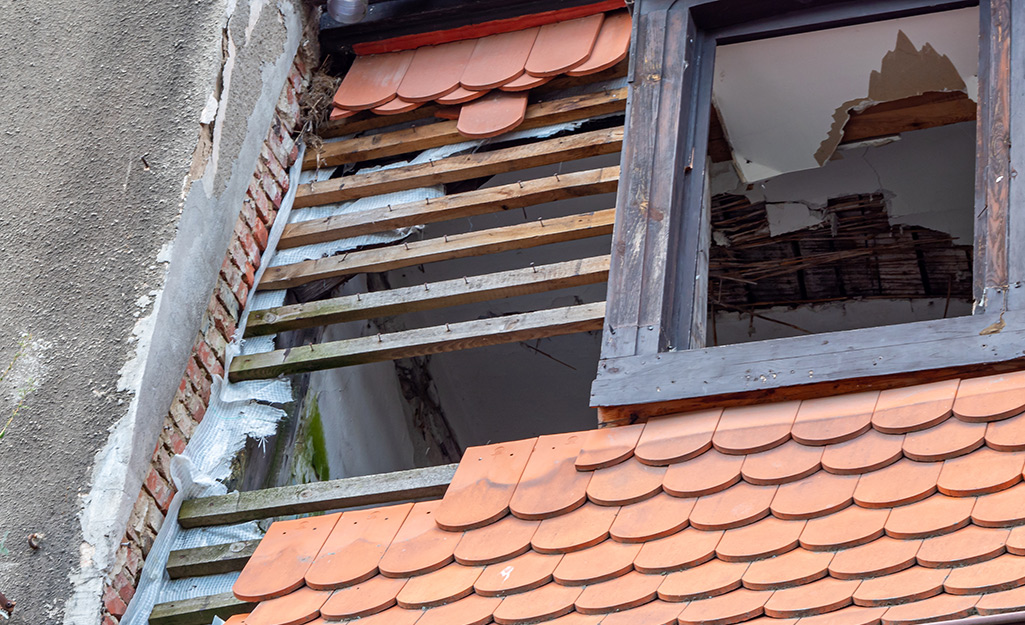 A roof and window with hurricane damage.