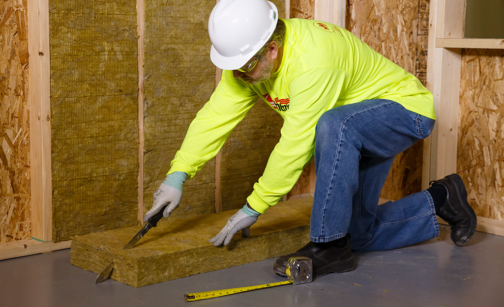 A person cutting an insulation batt to size to install between wall studs.