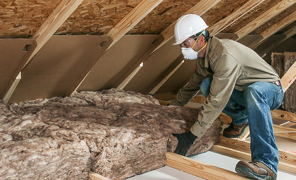A person installing fiberglass insulation batts in an attic.