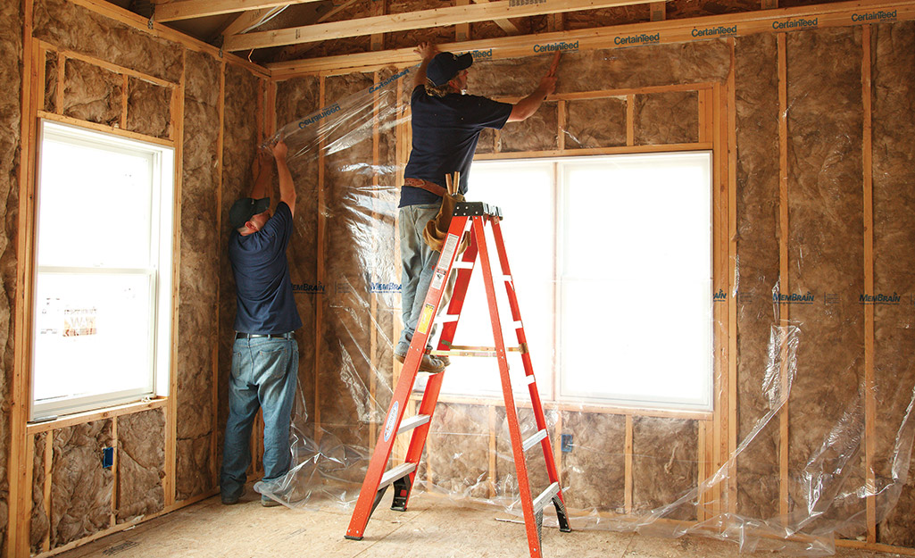 Two people installing a vapor barrier over batt insulation.