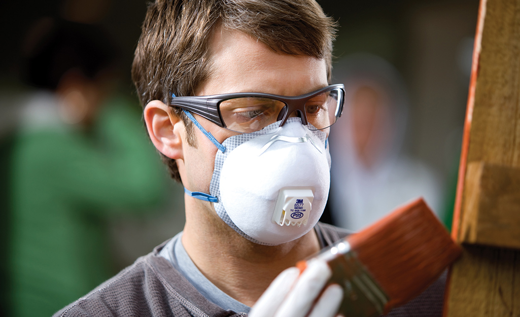A man wearing a respirator while staining wood.