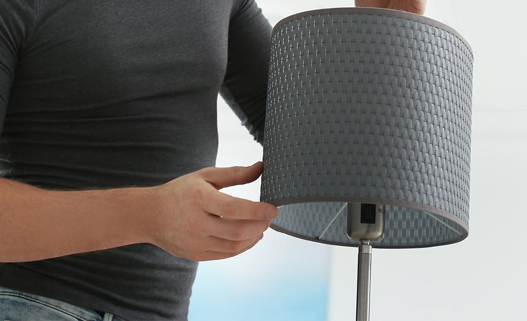 Một người đặt bóng đèn lên một ngọn đèn.