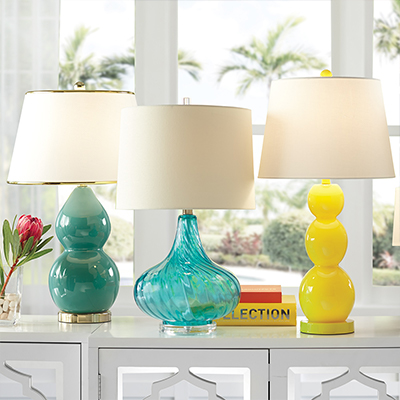 There glass lamps on a white table.
