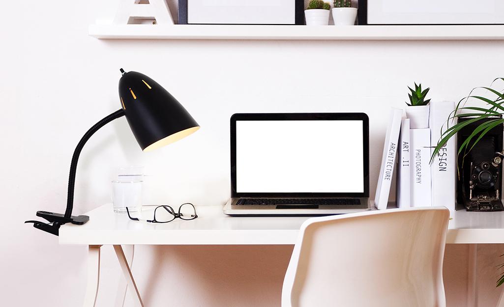 Đèn bàn cổ ngỗng kẹp được gắn vào bàn máy tính.