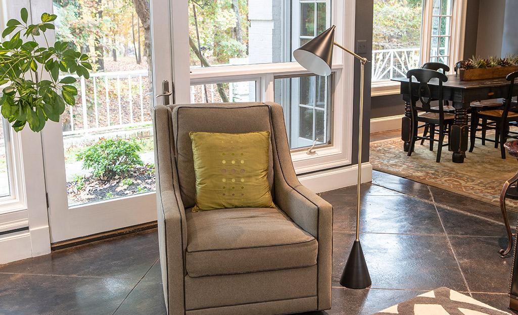 Một đèn sàn tác vụ kéo dài trên một chiếc ghế bành trong phòng khách.