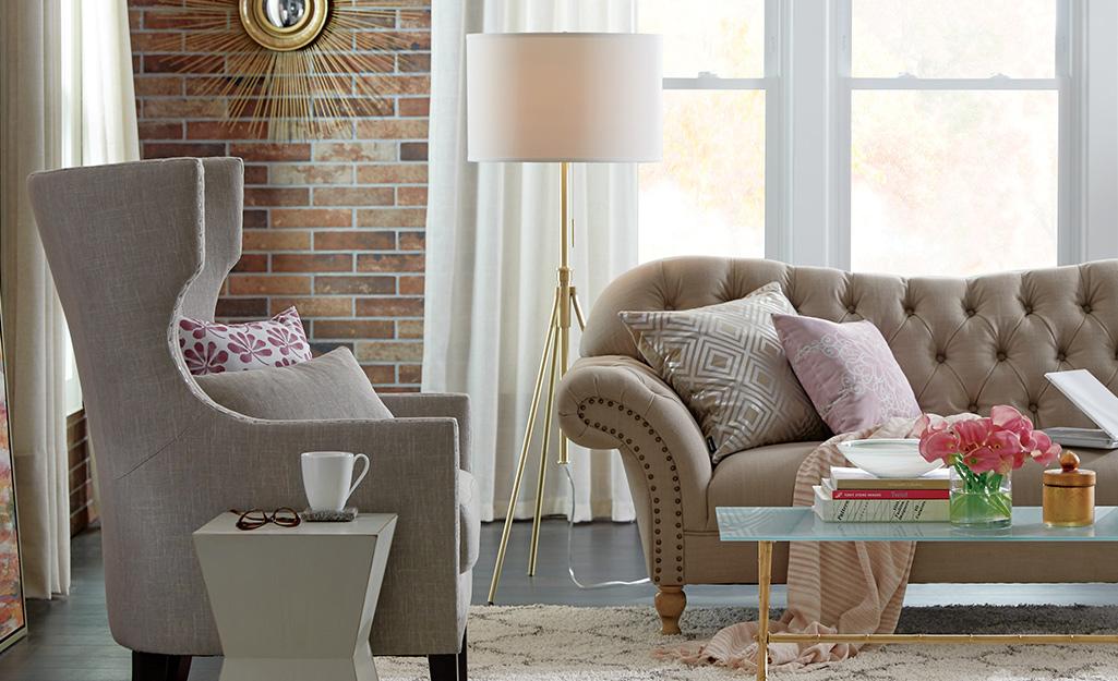 Đèn sàn có chân máy nằm sau ghế sofa và ghế bành trong phòng khách.