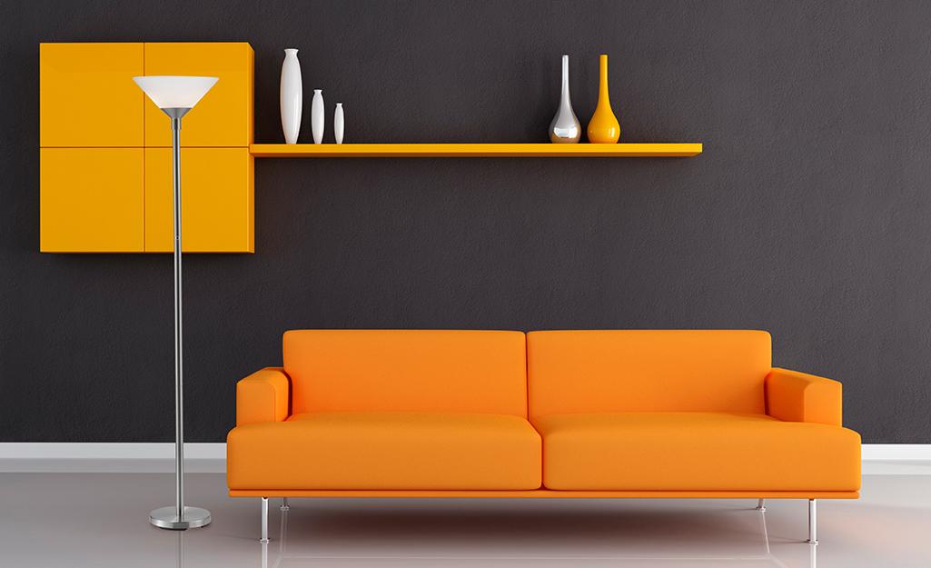 Đèn torchiere đặt cạnh ghế sofa màu cam hiện đại trong phòng khách hiện đại.