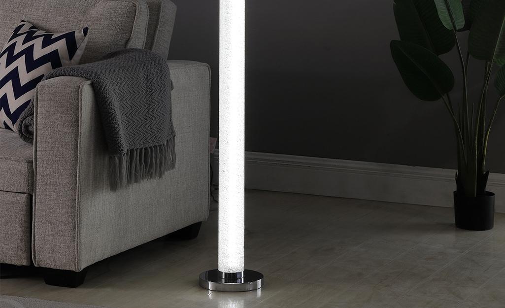 Một chiếc đèn cột tỏa sáng rực rỡ bên cạnh một chiếc ghế sofa.