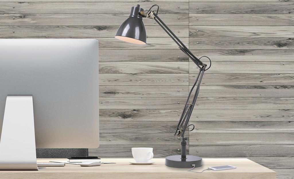 Đèn bàn có ổ cắm USB được kết nối và sạc điện thoại thông minh.