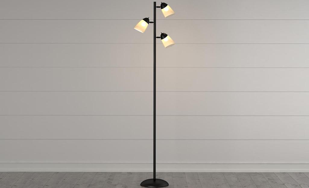 Đèn sàn cây với ba nhánh và đèn chiếu sáng trên bức tường ốp trắng.