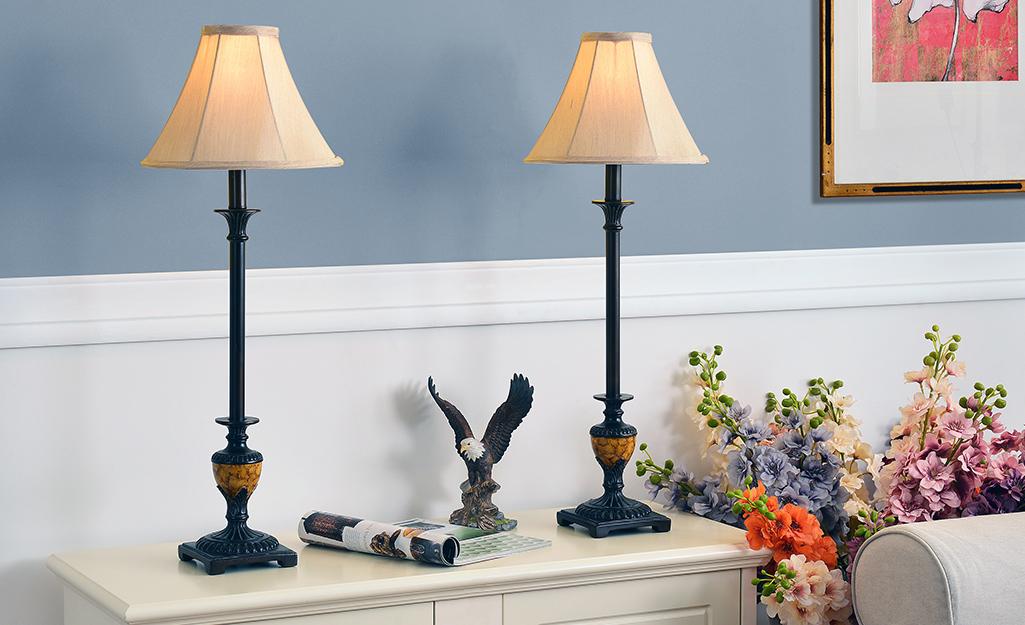 Hai chiếc đèn tự chọn cao đặt trên bàn bên trong phòng khách.
