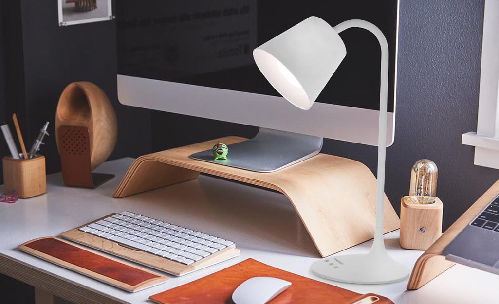 Đèn công việc vòng cung thắp sáng bàn máy tính.