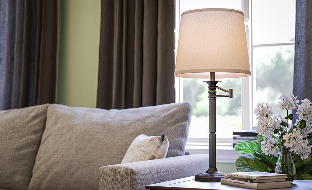 Đèn bàn có tay xoay đặt trên bàn cuối bên cạnh ghế sofa trong phòng khách.