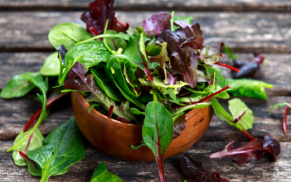 A bowl of mesclun mix on a wood table.