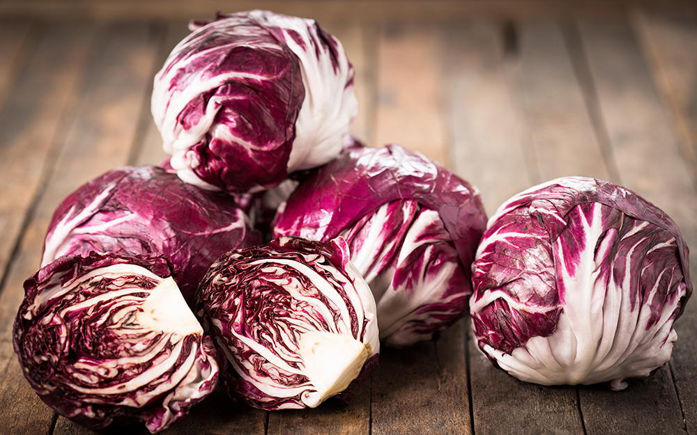 Several heads of radicchio on a wood table.