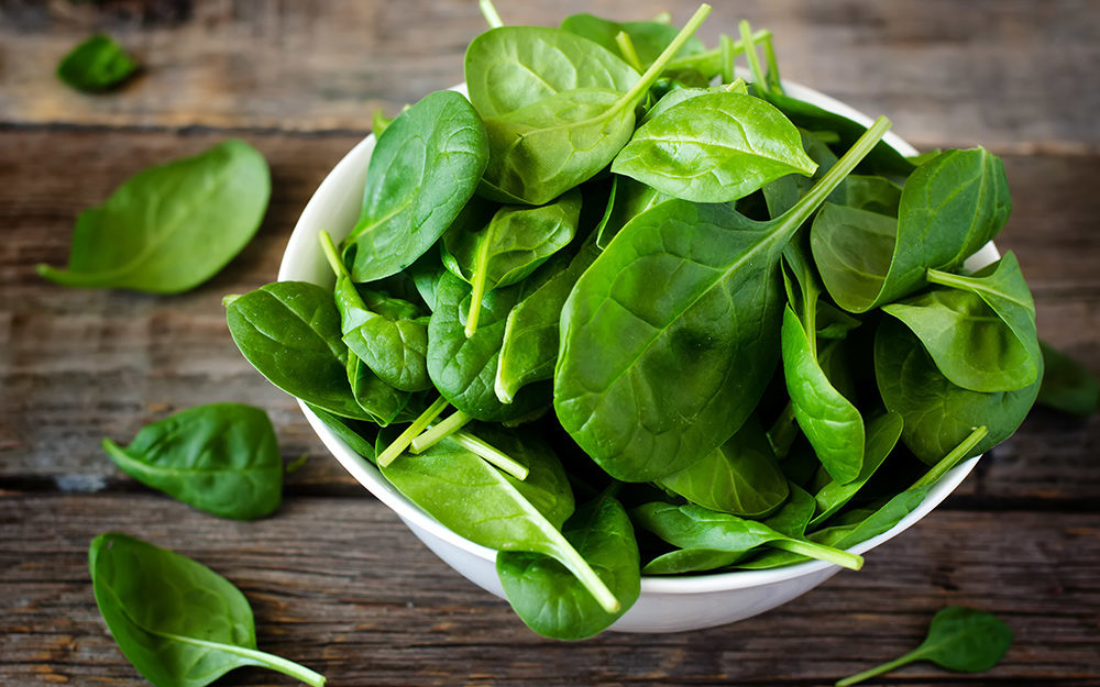 A bowl of spinach on a wood table.