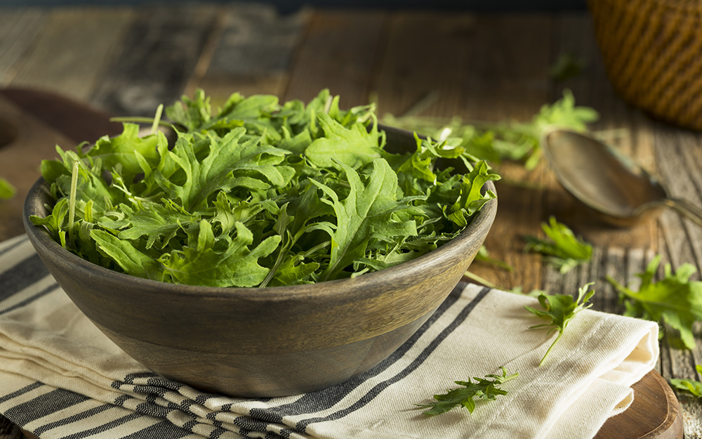 A bowl of baby kale on a table.