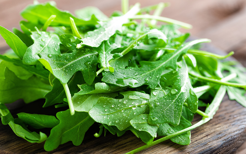 A pile of arugula on a wooden table.