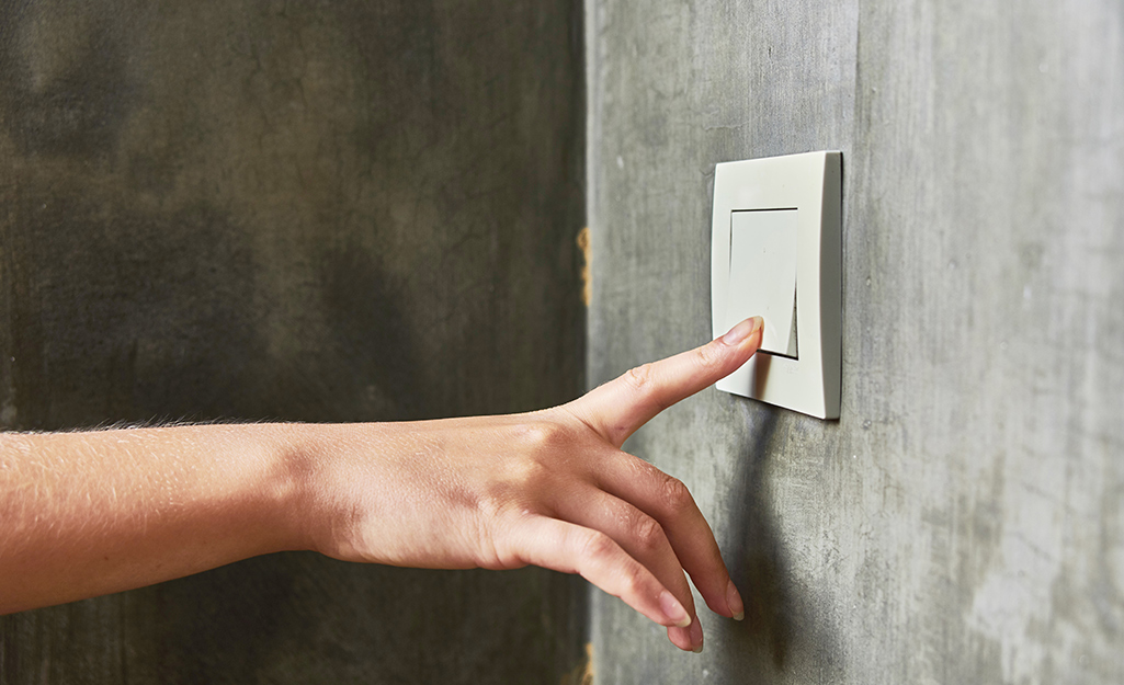 A person touching a touch light switch.