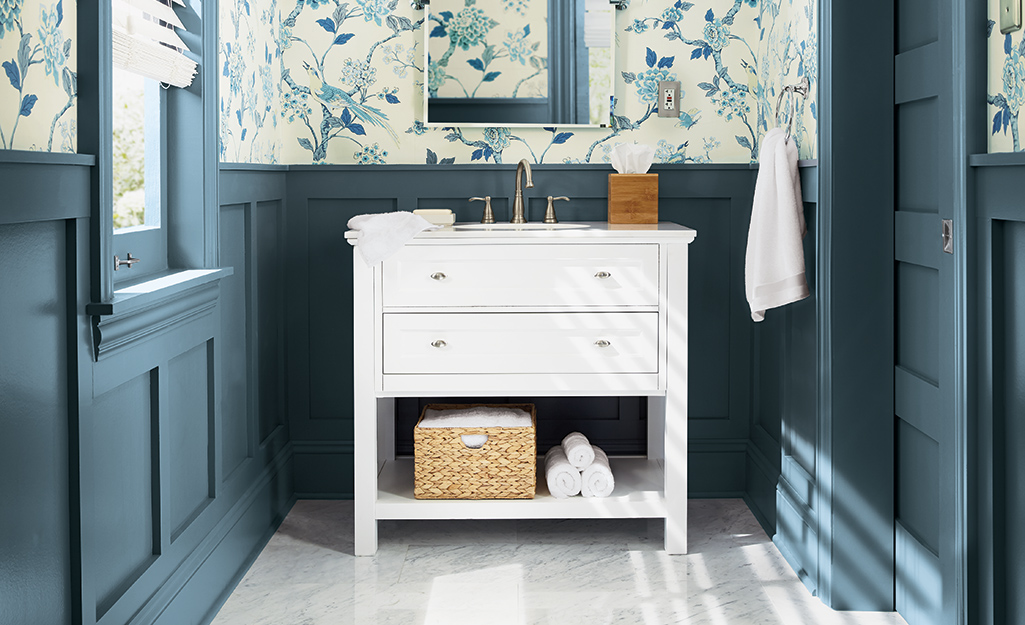 A bathroom with blue painted walls that feature moulding.