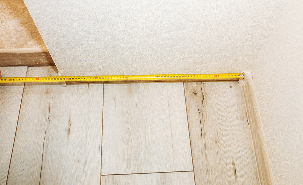 A tape measure being used to measure for moulding.