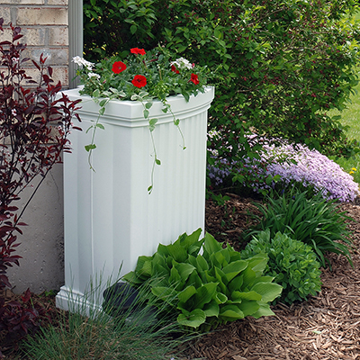 A white rain barrel with flowers planted on top beside a brick house.